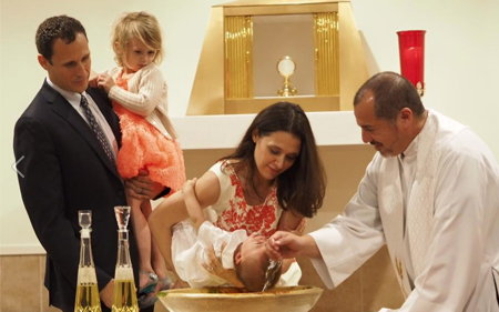 Father Mike baptizing Maria's baby