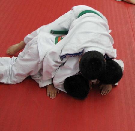 Young green belt kids doing matwork