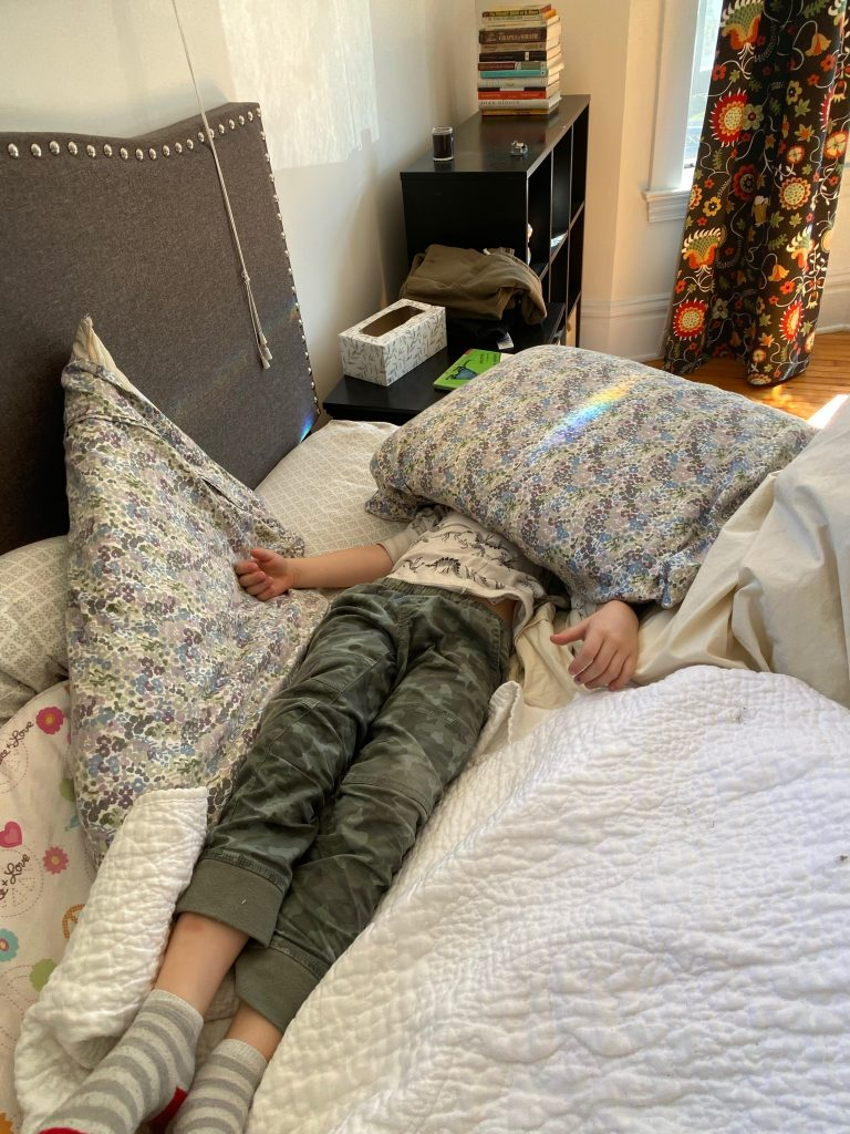 Student on bed with pillow over her head